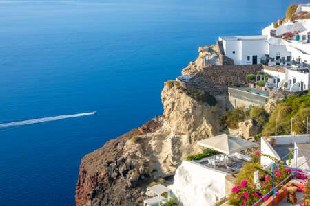 Greece. Sunny summer day in Santorini. Buildings and terraces with flowers on the caldera with seaview