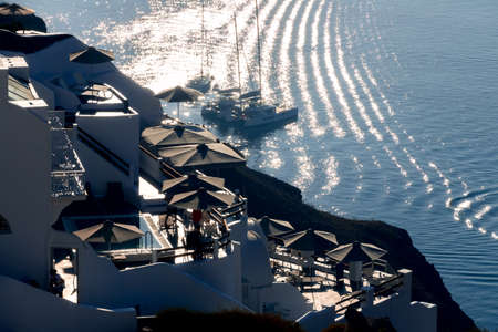 Greece. Evening at the Santorini caldera. Houses and terraces in the backlight of the sun. Sailing yachts at anchorage