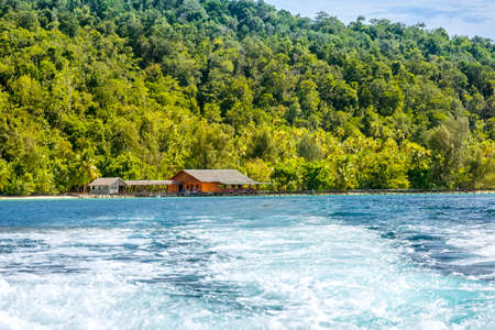Tropical island in Indonesia. Wooden pier and hut by the shore. Water foam behind the stern of the yacht