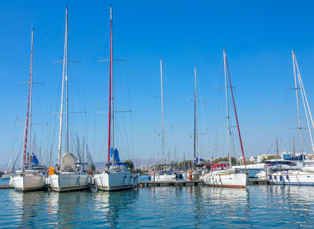 Sunny summer day. Small greek town. Many sailing yachts in a marina