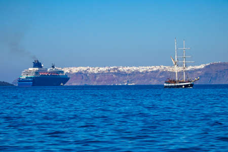 Greece. Sunny day off the coast of Santorini. Old three-masted ship and multi-deck cruise ship