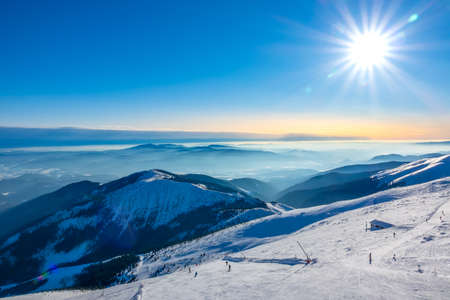 Winter Slovakia. Ski resort Jasna. View from the top of the snow-capped mountains to the ski slope with skiers 写真素材