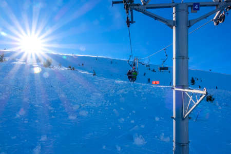 Winter Slovakia. Ski resort Jasna. Bright sun over ski slope. View from the chair lift