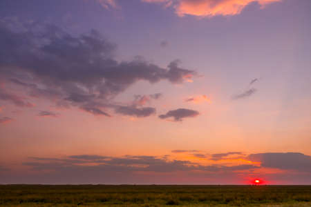 Summer colorful sunset with illuminated clouds over steppe plain