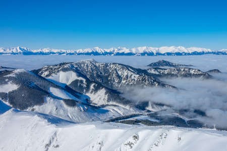 Ski resort Jasna. Winter Slovakia. Panoramic view from the top of the snow-capped mountains and fog in the valleys 写真素材