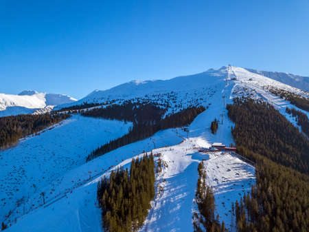 Winter Slovakia. Jasna in sunny day. Ski slopes in the wooded mountains. The sun shines brightly in the blue sky. Aerial view
