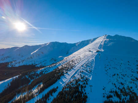 Slovakia. Ski resort Jasna in sunny winter weather. Ski slopes in the wooded mountains. The sun shines brightly in the blue sky. Aerial view 写真素材