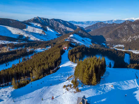 Slovakia. Sunny winter day at the Jasna ski resort. Blue sky. Mountain peaks and ski slopes. Aerial view 写真素材