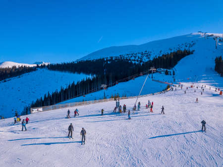Slovakia. Winter Jasna in sunny day. Ski slopes in the wooded mountains. Sun shines brightly and blue sky. Aerial view
