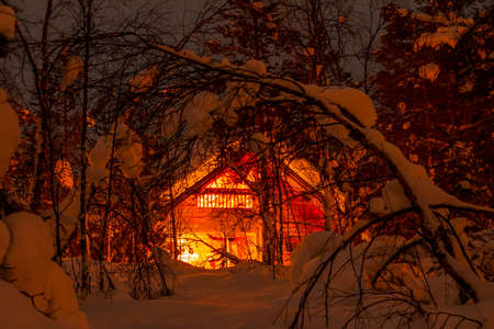 Winter Finland. Thick forest and a lot of snow. Small wooden house and night lighting 写真素材