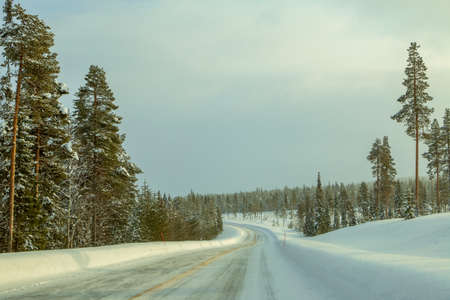 Winter Finland. Wooded hills and a lot of snow. Empty highway with drifts on the side. Weak northern sunlight 写真素材