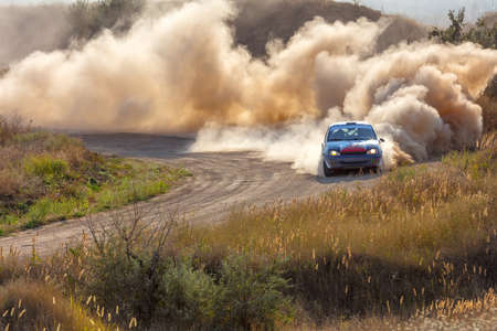 Sunny summer day. Dusty rally track. Sports car does a lot of dust in turn 06