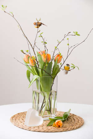 cristal: Fresh spring bunch of orange tulips and green leaves and two small birds in a nice cristal glass vase and a cute heart symbol on the straw board and table with a tablecloth. Home decor for spring and Easter. Beautiful flowers.