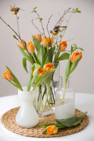 cristal: Fresh spring bunch of orange tulips and green leaves and small birds in nice cristal glass vases on the straw board and table with a tablecloth. Home decor for spring and Easter. Beautiful flowers.
