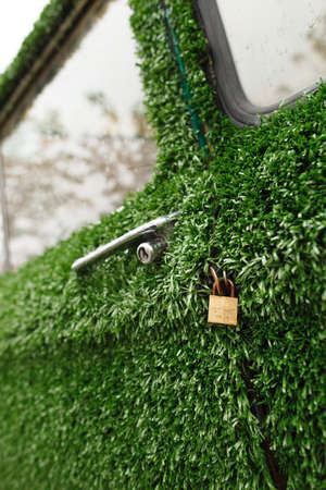 idea generation: A gold lock on an old green grass decorated car. Funny and ecological design idea for a car decoration. New generation of future cars.