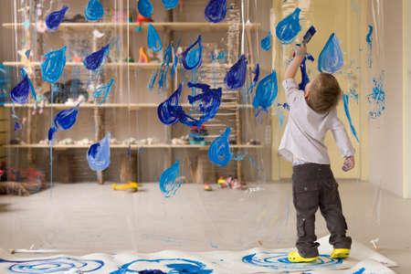 흰 셔츠에 3 세 소년 파란색의 비가 드로잉입니다. 집에서 재미 있고 창조적 인 어린이 활동. 실내 어린이들을위한 봄 여가 활동.