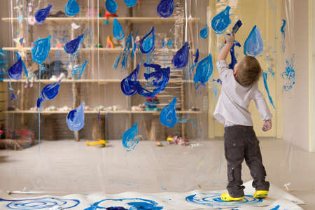 A 3 years old boy in a white shirt is drawing blue drops of rain. Interesting and creative  kids activities at home. Spring leisure activities for children indoors.
