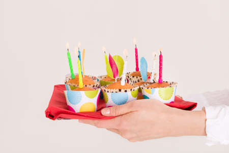 childs birthday party: Womans hands holding a bright tray with muffins and birthday candles. Homemade sweet present for a childs party. Celebration of a birthday.