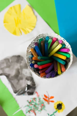 child's drawing: Set of bright colorful pens in a white pot with a childs drawing. Creativity for kids. Colors of childhood