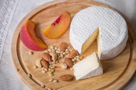 pinoli: delizioso formaggio fatto in casa camambert bianco su un piatto di legno servito con mandorle, anacardi, pinoli e pesca. Dessert per una cena in famiglia.