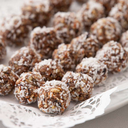 White plate full of delicious raw protein balls. Healthy sweets for sport people. Homemade dessert. Raw sweets made of nuts, coconut, dates and cacao