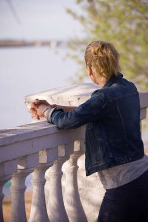 denim jacket: Young blond girl in blue denim jacket standing at the railing and watching the Volga river.
