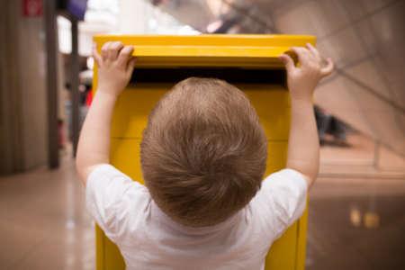 흰색 t- 셔츠에 작은 금발 소년 노란색 postbox에 편지를 놨 어 요. 우체국의 친구에게 우편을 보냅니다.