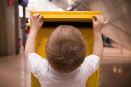 A little blond boy in a white t-shirt puts a letter into a yellow postbox. Sending post to a friend at the post office. Stock Photo