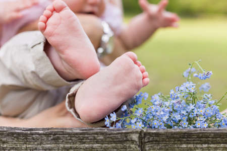 bare feet girl: Bare feet of a cute baby on the wooden background. Forget me not and a child. Childhood in the farm. Retro style image of infant and flowers.Small bare feet of a little baby girl.