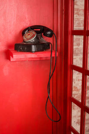 ancient telephone: Red Telephone booth in English style. British phone box with black retro telephone standing in it. Vintage looking Red telephone box.