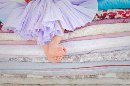bare feet girl: Decorations for fairy tale Princess and the Pea. Little girl with bare feet sitting on the pile of blankets and mattresses. Child in a lilac fluffy skirt at the party. Girls birthday. Stock Photo