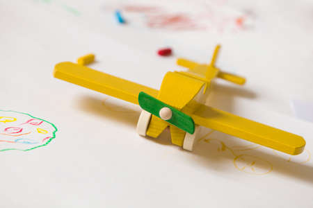 kindergarden: Yellow wooden toy plane on the white background. Education, children, play concept. Kids drawings with the toy. Childhood. Happy. Joy. Kindergarden.