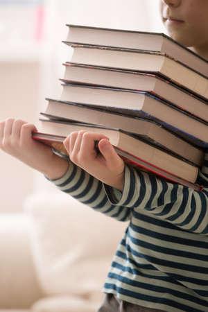 도 서의 더미를 들고 스트라이프 셔츠에 어린 소년. 교육 및 지식 개념입니다. 어린이 읽기. 학교로 돌아가다. 행복한 독서. 도서관에서 모범생입니다.