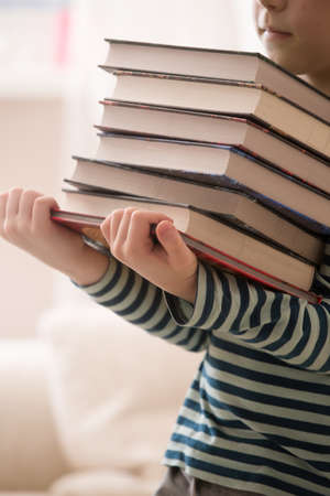 striped shirt: Little boy in a striped shirt holding a pile of books. Education and knowledge concept. Reading children. Back to school. Happy reading. Schoolboy at the library.