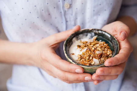 cereals holding hands: Young woman with muesli bowl. Breakfast cereals with nuts, pumpkin seeds, oats and Yogurt in bowl. Hands holding homemade granola. Healthy snack.