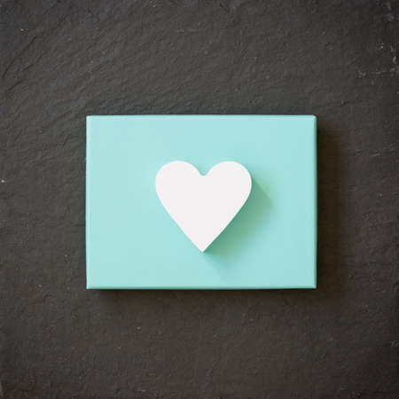 tiffany blue: White heart on a turquoise color box on black background. Valentines day. Present. Gift.