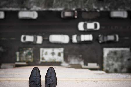 지붕의 가장자리에 서있는 사람의 피트의 확대합니다. 높은 건물의 발코니에 남자의 부츠에 상위 뷰. 우울증과 불안의 개념입니다. 위기.