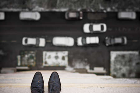Close-up of mans feet standing on the edge of the roof. Top view on mans boots on the balcony of high building. Depression and instability concept. Crisis. Stock Photo