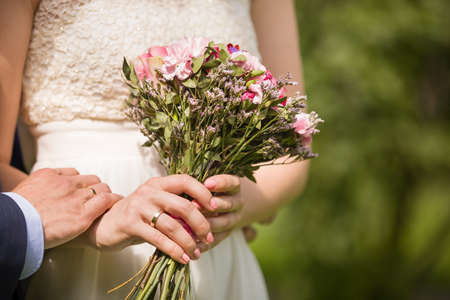 newly married couple: Close-up of bride and groom holding hands. Wedding outdoors. Newly married couple - wedding details. Just married. Stock Photo