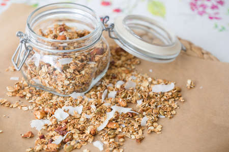 Glass jar of homemade organic granola with coconut and pecans on the baking paper background. Delicious breakfast cereal. Healthy muesli. Stock Photo