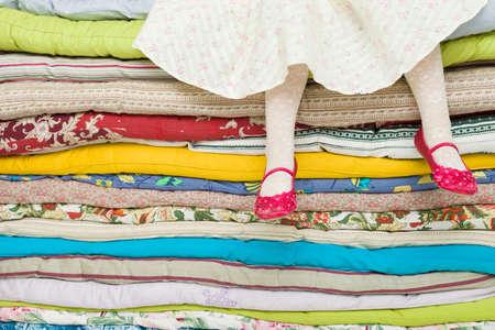 """다채로운 매트리스의 더미에 앉아 어린 소녀의 다리. 동화 장식 """"완두콩의 공주"""""""
