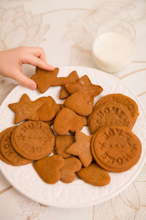 circuses: A hand of a child taking freshly made home holiday cookies in shapes of starts, hearts and circuses. Plate of Christmas treats. Dessert for a family.