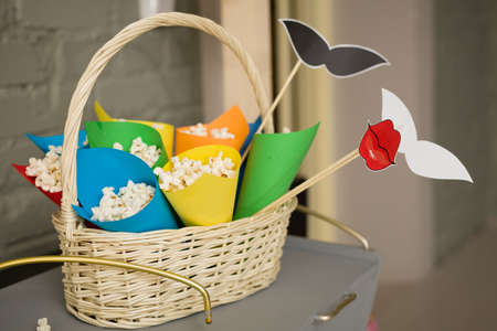 mustaches: Pop corn in colorful paper cones in a white basket.  Preparations for a party.accessories for a fun holiday of paper, lips, mustaches.