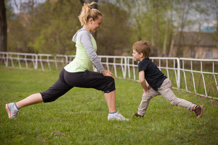 outdoor training: Happy son and mother are doing exercises in the summer park. on the stadium, outdoor. Sport activities with children. Healthy lifestyle. Fitness exercises. Young mother and son are stretching together