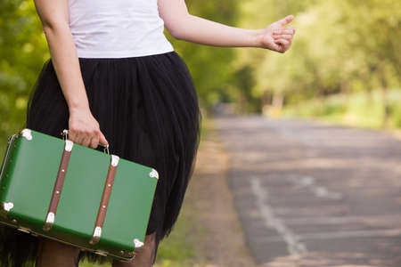gentle dream vacation: A young girl in a white tank top and black fluffy skirt (tutu skirt) catching a car on the countryside road. Traveling with a green retro suitcase. Car drive. Catching a taxi in the park outdoor.