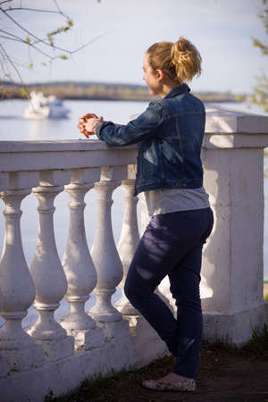 volga river: Young blond girl in blue denim jacket standing at the railing and watching the Volga river.