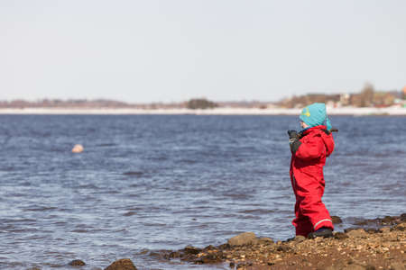 jumpsuit: A small cute baby boy in a red jumpsuit and blue hat standing on the river shore and watching water. Spring walks on the river beach. Outdoor.