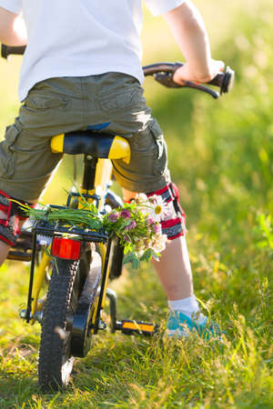 Close up of little kid boy riding on his bicycle  with flowers, outdoors. Boy riding his first yellow bike on a meadow. Leisure activities for children outdoors. Summer time. Happy summer concept