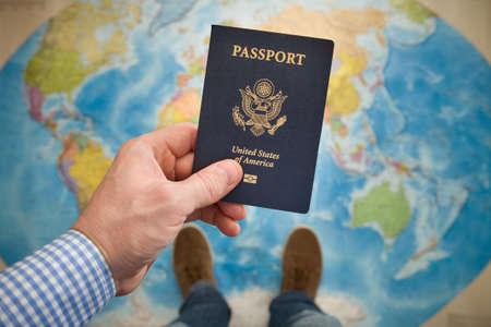 Man's hand met Amerikaans paspoort. Kaart achtergrond. Klaar om te reizen. Open wereld. Stockfoto