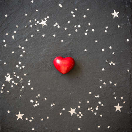 silver stars: Small red heart on the black background with silver stars. Hearts and stars on a black board. Background. Valentines and Christmas.